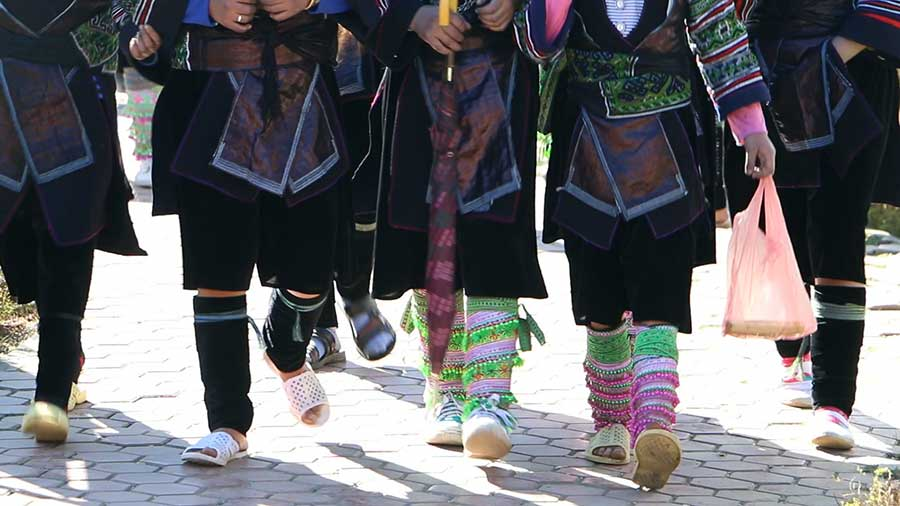 Hmong girls in their beautiful costume walking (leg shot)